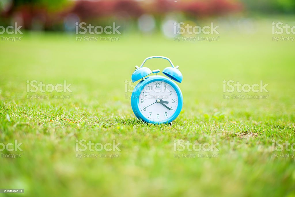 Summertime.  clock on grass stock photo