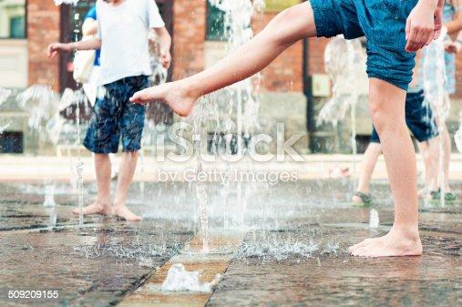 Summertime enjoyment. Kids legs and feet wet in fountain. Outdoors.