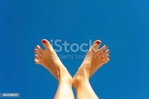 700603062istockphoto Summertime enjoyment. Woman feet on blue sky background. 494598031