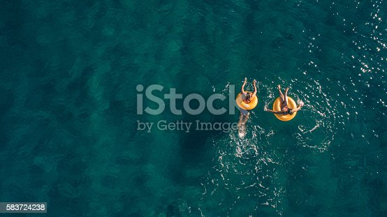 High angle view photo of a two young women relaxing while floating in the ocean using swimming tubes; wide photo dimensions