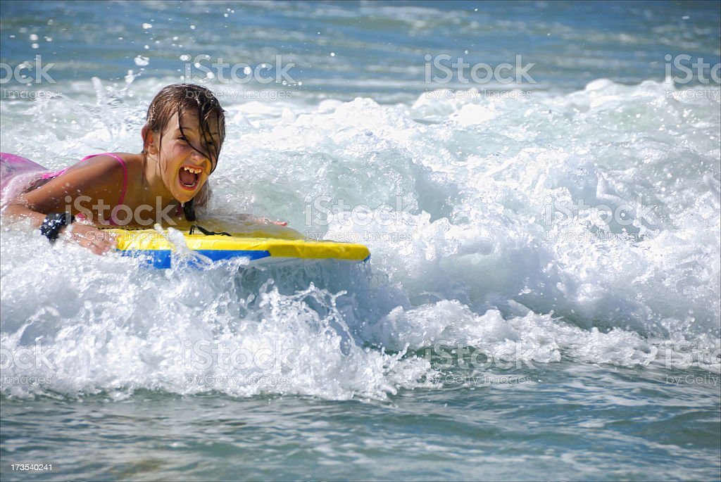 Summertime - Girl Catching a Wave at the Beach stock photo