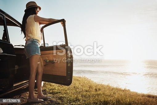 Shot of a young woman enjoying a road trip along the coast