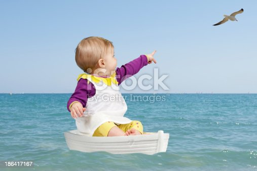 summertime : little toddler in a boat on the ocean