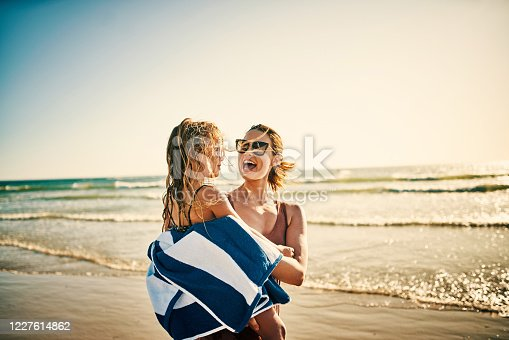 Shot of a young woman wrapping her adorable little girl in a towel at the beach