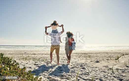 Rearview shot of a little girl and her parents spending time together at the beach
