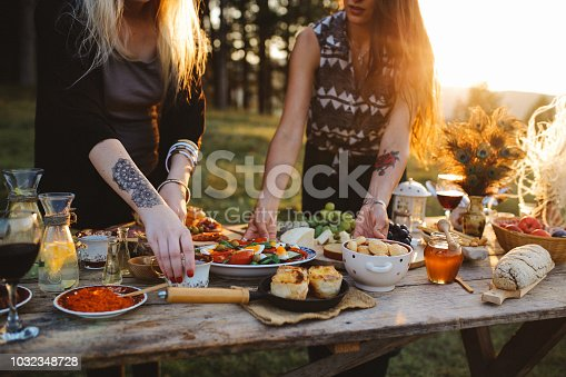 Close up on the picnic table, two women are preparing food and drink on a beautiful summer day. Various foods on an old, rustic, wooden table.