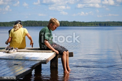 Children cool their feet and relax on a dock by the lake in Janakkala, Finland.