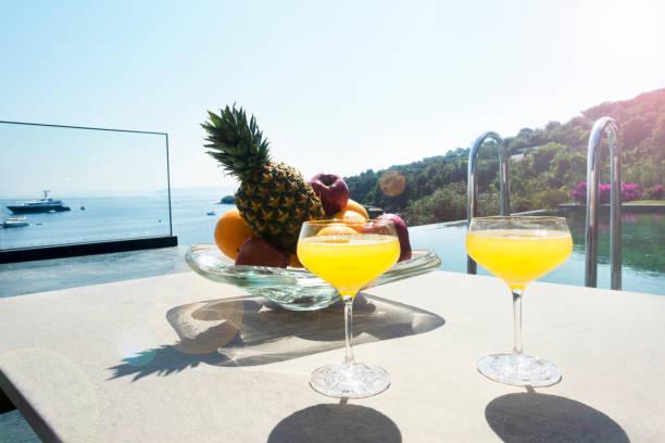 Sommerliche Erfrischung, Cocktails und frisches Obst neben dem Pool – Foto
