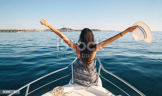 Young woman enjoying the vacation on the seaside, sitting on the front boat deck with her arms outstreched, watching the small town of Rovigno on the horizon. Happiness, summertime concept in vintage color grading.