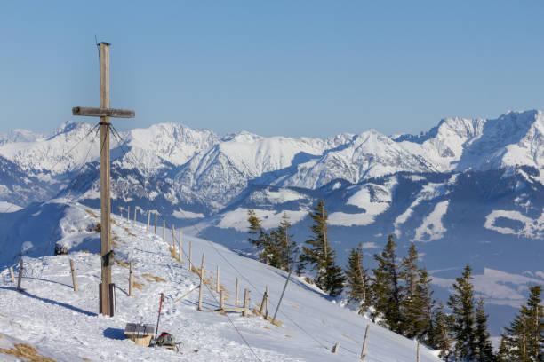 summit cross in winter with outlook to a mountain range. - bayerische brotzeit stock-fotos und bilder