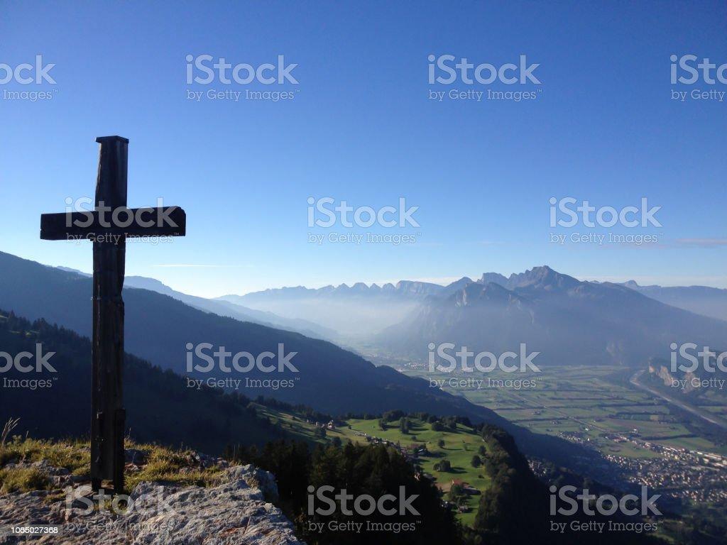 Gipfelkreuz auf einem hohen alpinen Berggipfel in der Schweiz mit einem tollen Blick auf die Täler und Dörfer unten und dunstigen Berge hinter – Foto
