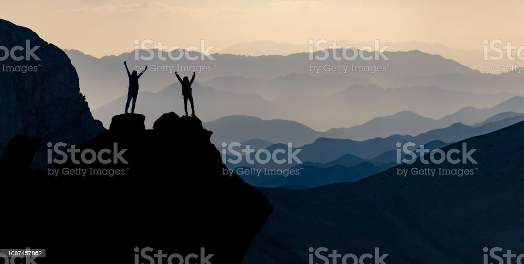 summit of successful female mountaineers stock photo