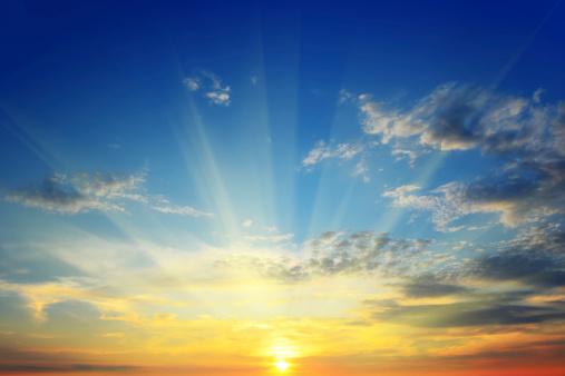 sun rays illuminate the sky above the horizon