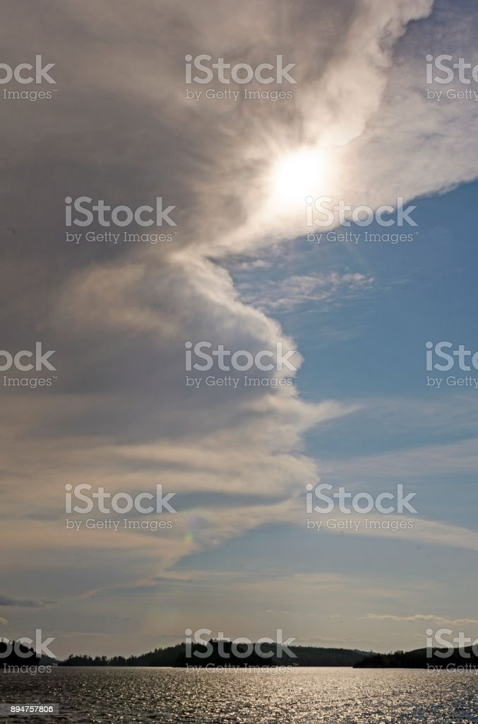 Sun and Clouds over a Lake stock photo