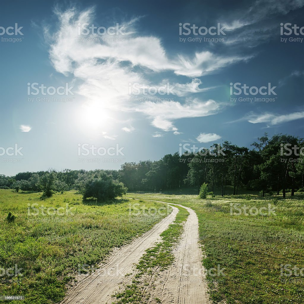 sun and clouds over road to wood royalty-free stock photo