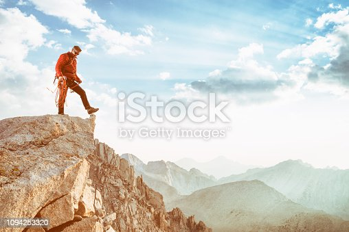 A man climbs and hikes in the high Sierra Nevada mountains during a beautiful sunset.