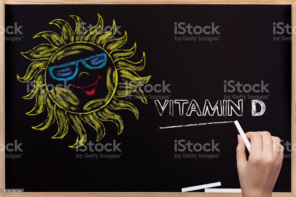 Sun and Vitamin D written on blackboard stock photo