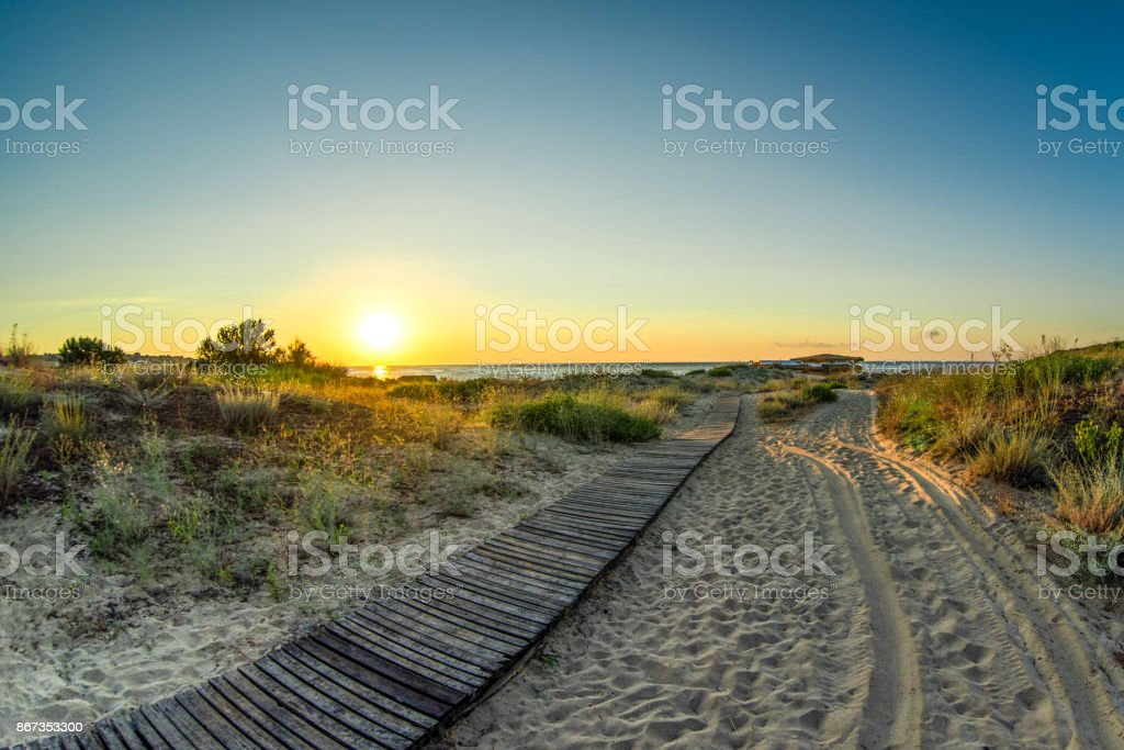 Sun at the horizon lights wooden boardwalk over the sand dunes to wild beach stock photo