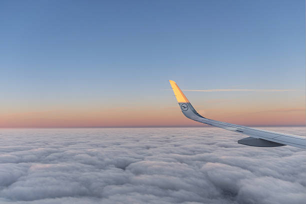 sun at the wing of an aircraft flying in sunrise - lufthansa stock-fotos und bilder