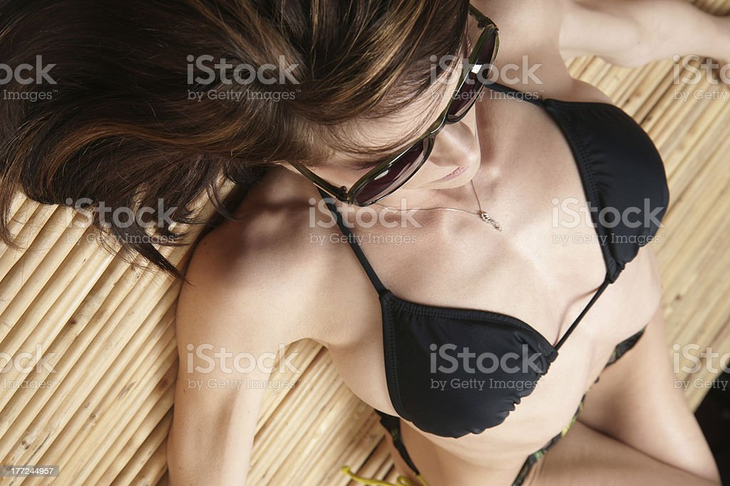 Sun Bathing Enjoyed on Bamboo by Buxom Bikini Laden Female royalty-free stock photo