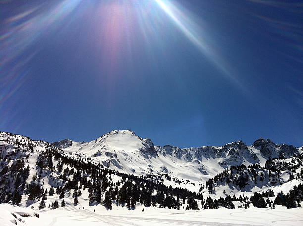 Sun beam over snow capped mountains stock photo