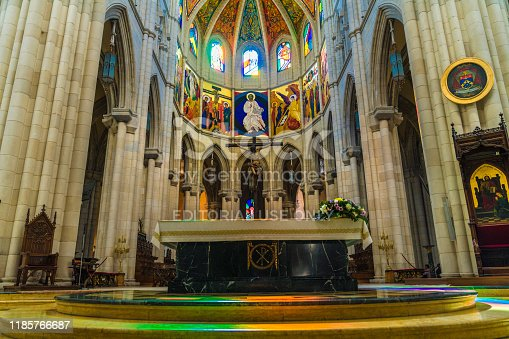 This epic image shows sun beaming in through cathedral stained glass in Santa María la Real de La Almudena casting colorful designs on the buildings floor.