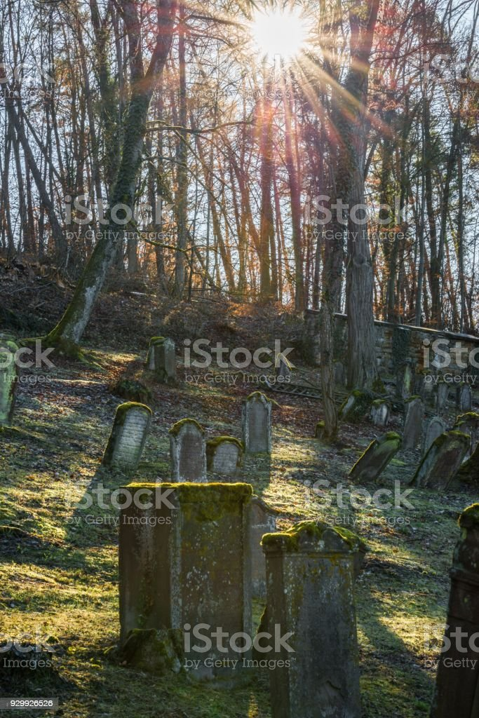 Sun beams at old Jewish cemetery with weathered tombstones, Germany stock photo