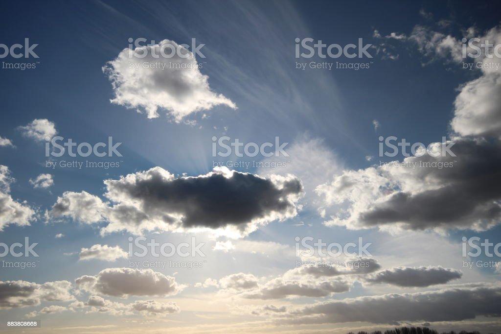 Zon balken komt achter de wolken in de blauwe hemel foto