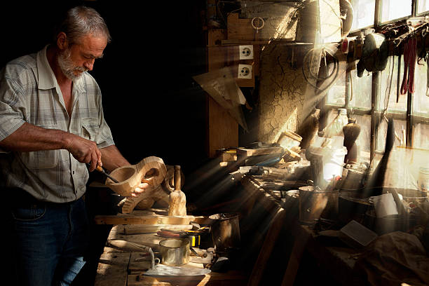 Sun beams shining on carpentry Summer sun beams shining on the hands of a skilled carpenter carving craft product stock pictures, royalty-free photos & images