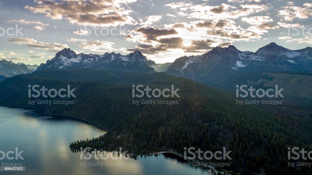Sun begins to set over the mountains of Idaho at Radfish Lake stock photo