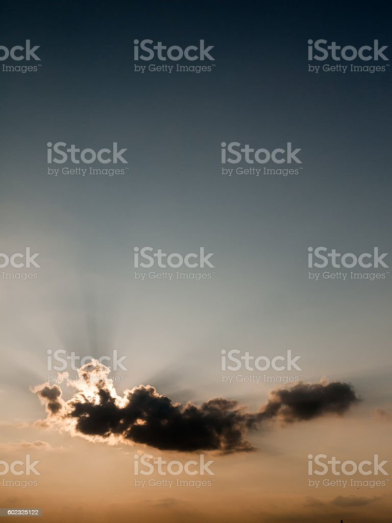 Sun behind a single cloud formation stock photo