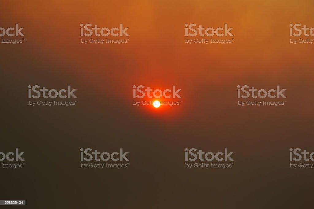 Sun behind smoke clouds stock photo