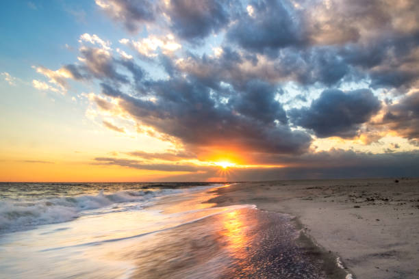 Sun breaking through dark clouds over a beach during sunset. Warm golden light contrasts a stormy sky on the coastal scene.
