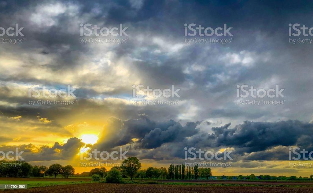 Golden sun breaking through the dark grey threatening storm clouds...