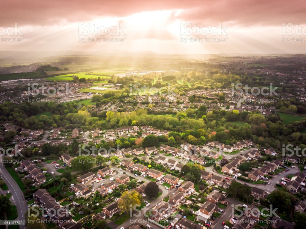 Sun bursting through clouds over traditional British houses with countryside in the background. stock photo