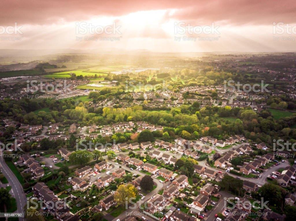 Soleil éclatant à travers les nuages au-dessus des maisons traditionnelles britanniques avec paysage en arrière-plan. - Photo