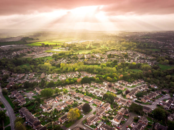 Sun bursting through clouds over traditional British houses with countryside in the background. - foto stock