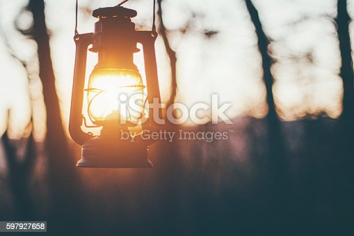 Old lantern hanging in forest, sun shining insted of fire