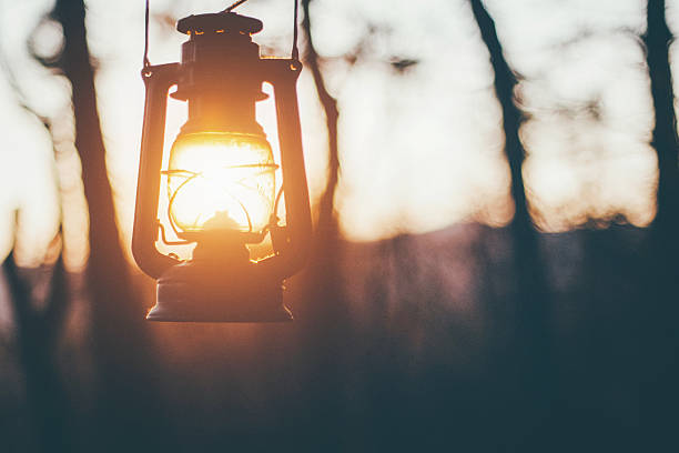 Sun captured in old lantern Old lantern hanging in forest, sun shining insted of fire lantern stock pictures, royalty-free photos & images