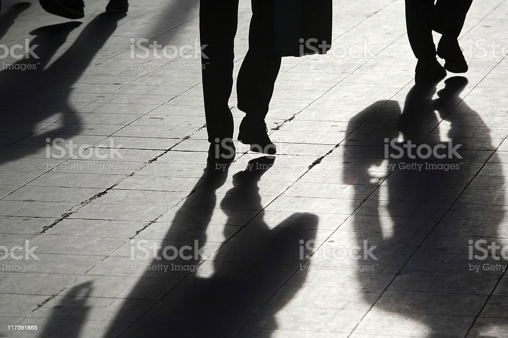 sun casting shadow over people walking on the street royalty-free stock photo