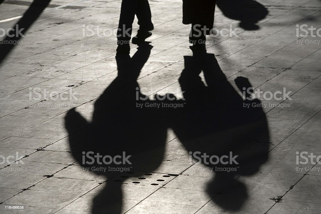 sun casting shadow over two people walking on the street