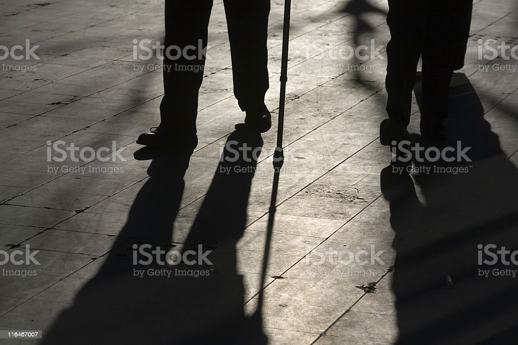 sun casting shadow over two people walking on the street royalty-free stock photo