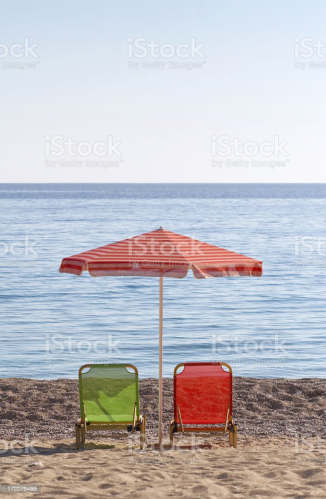 Sun chairs and umbrella on beach royalty-free stock photo