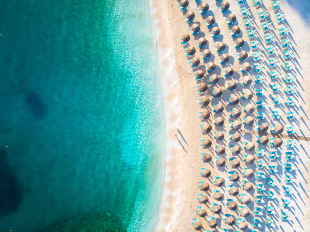 Sun chairs and umbrellas beach with no tourists and clear blue water stock photo