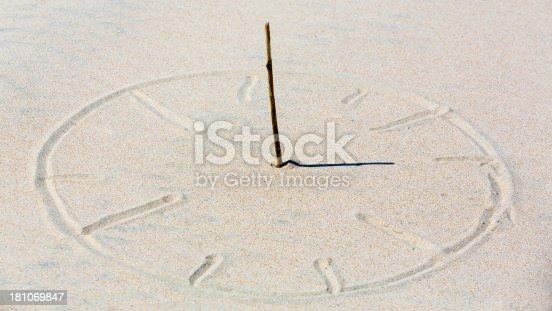 Sun clock in beach sand.