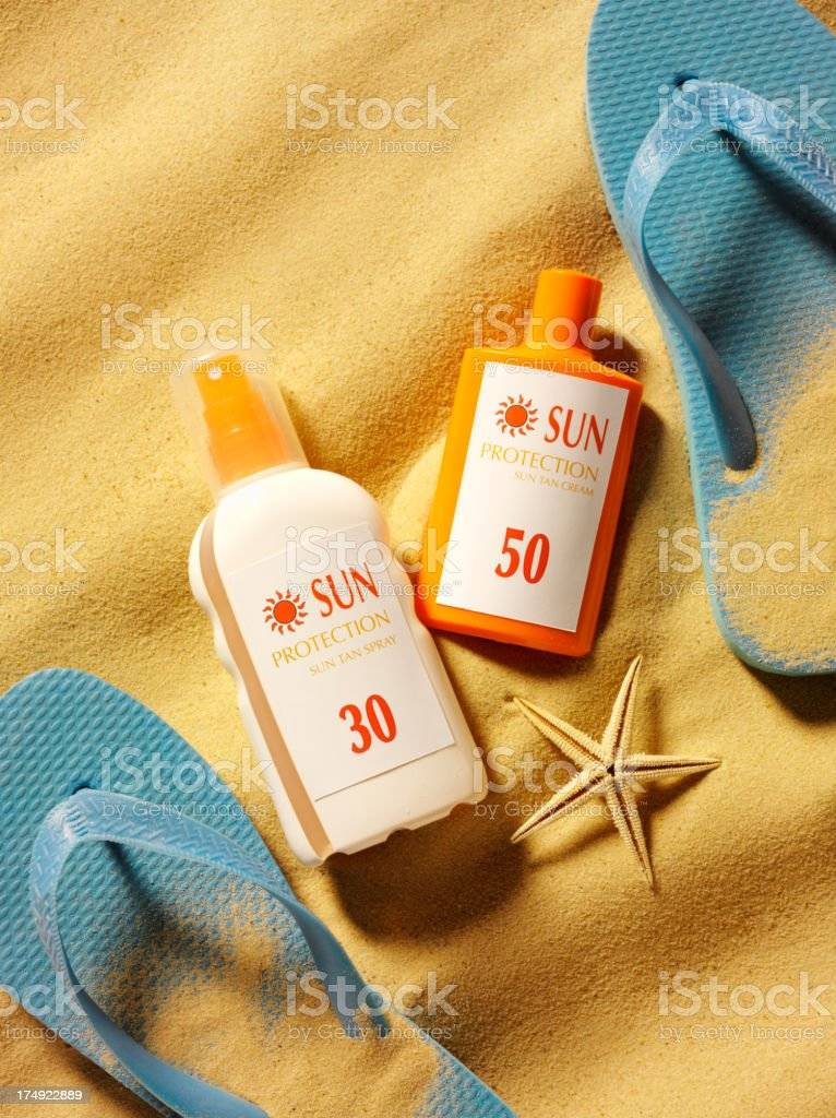 Sun Cream Protection with Blue Flip Flops on the Beach royalty-free stock photo