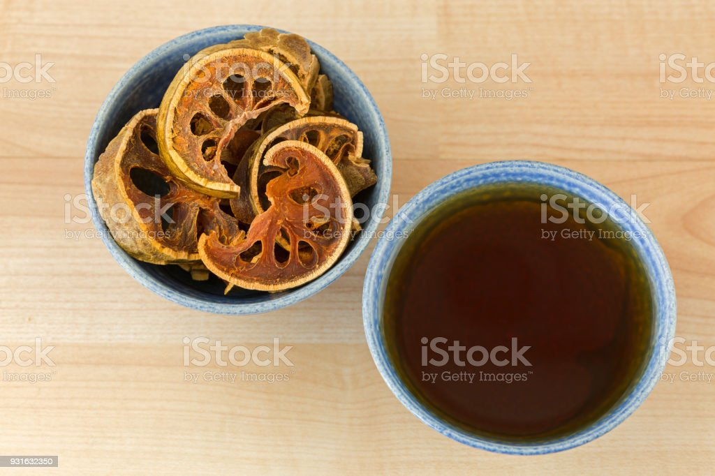 Sun Dried Bael Fruit in bowl next to cup of hot Bael herbal tea, also called Stone Apple stock photo