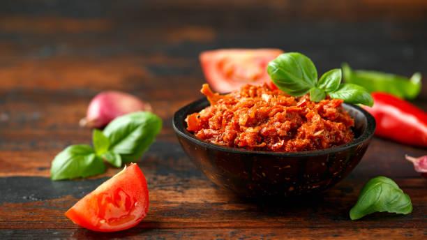 Sun dried tomato pesto with chilli, garlic and herbs in bowl stock photo