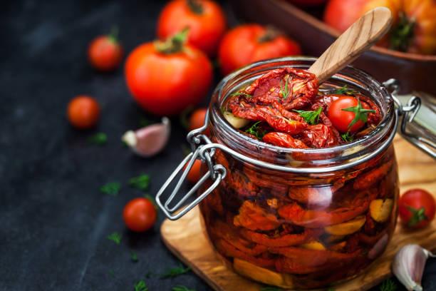 zon gedroogde tomaten met knoflook en olijfolie - gedroogd voedsel stockfoto's en -beelden