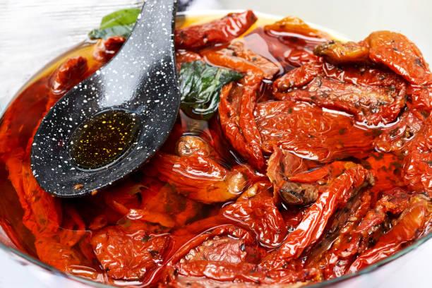 tomates secos al sol con aceite de oliva en un tazón blanco con cuchara negra - foto de stock